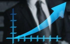 imagem de um homem de social com um elemento gráfico de seta azul para ilustrar a postagem de investir em ações