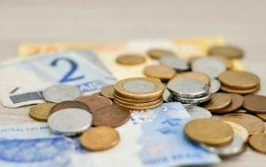 Imagem de moedas e cédulas para ilustrar post sobre conta salário