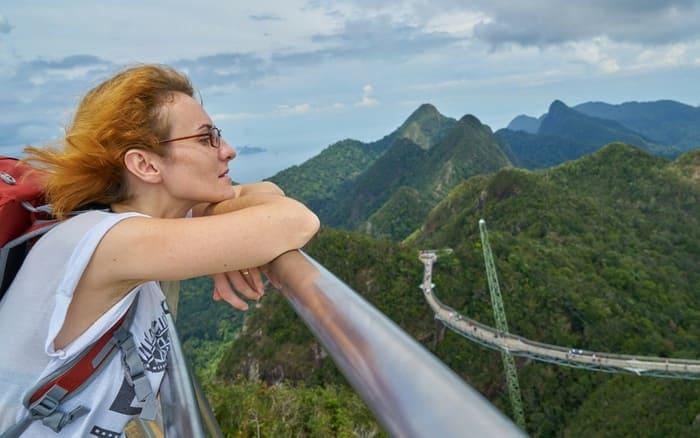 Imagem de mulher curtindo a paisagem para ilustrar post sobre mulheres compram mais seguro viagem