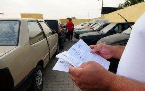 Imagem de motorista com papéis para ilustrar post sobre consultar multas de trânsito