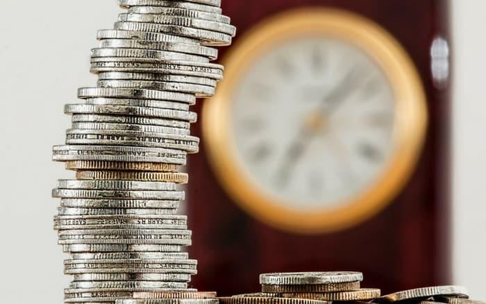 Imagem de moedas e relógio para ilustrar post sobre qual o melhor investimento a longo prazo