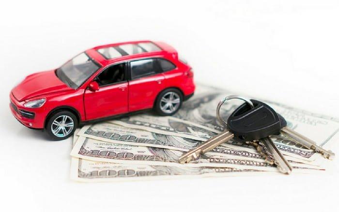 Imagem de uma miniatura de carro e chave de carro em cima de notas de dinheiro para ilustrar a postagem de como funciona consórcio de carro
