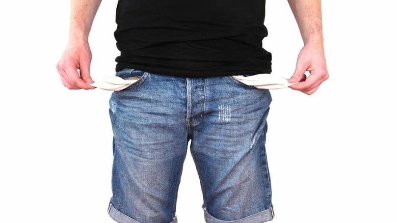 Imagem de homem segurando bolso vazio para ilustrar post sobre Como sair das dívidas