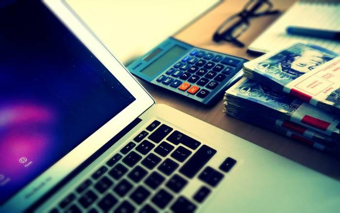 Imagem de notebook e dinheiro para ilustrar post sobre transações bancárias