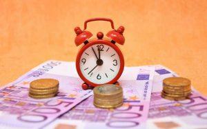 Imagem de dinheiro e relógio para texto sobre imposto de renda sobre investimentos