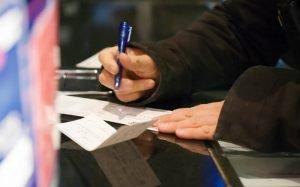 Imagem de pessoa assinando cheque para ilustrar texto sobre como preencher cheque