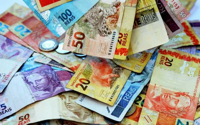 Imagem de notas de dinheiro ilustrando texto sobre diferença entre renda fixa e renda variável.