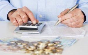 Imagem de calculadora, papel e dinheiro ilustrando texto sobre consultar o score serasa.