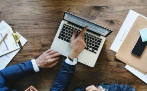 Imagem de pessoas no computador ilustrando texto sobre dicas de investimento