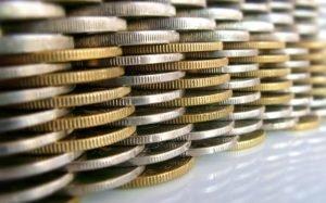 Imagem de moedas ilustrando texto sobre investimento com baixa automática
