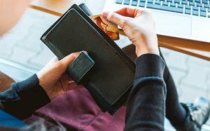 Imagem de pessoa com cartão de crédito na mão ilustrando texto sobre cartão de crédito para empresa