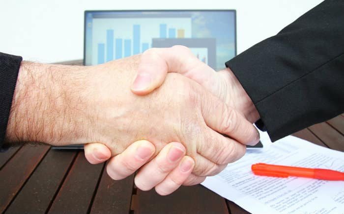 Imagem de aperto de mãos fechando negócio para ilustrar texto sobre empréstimo para abrir empresa