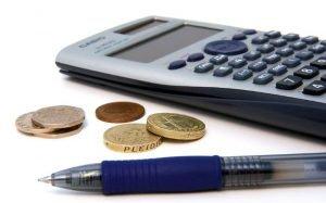"""Imagem de calculadora e moeda ilustrando texto sobre """"Fiz um empréstimo e não paguei. E agora?"""""""