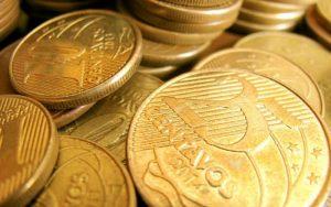 Imagem de moedas ilustrando texto sobre empréstimo para funcionário público