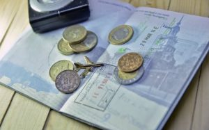 Imagem de passaporte e moedas ilustrando texto sobre empréstimo para viajar