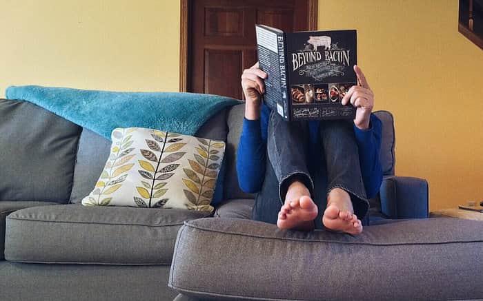 Imagem de pessoa lendo no sofá para ilustrar texto sobre orçamento para morar sozinho