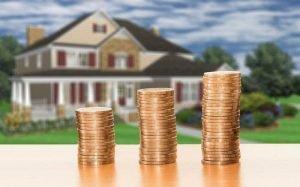Ilustração de casa e moedas de dinheiro para texto sobre consórcio imobiliário vale a pena