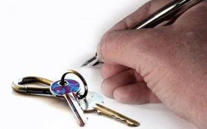 imagem de mão assinando um papel e chave para ilustrar texto sobre transferir consórcio