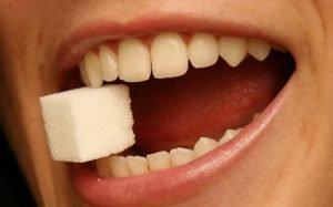 imagem de sorriso e acúcar para ilustrar texto sobre o que é restauração dentária