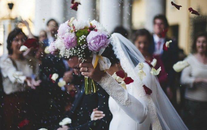 Noiva com buquê na mão comemorando casamento