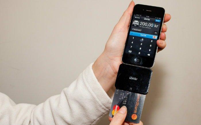 Imagem de maquininha de cartão ligada no celular para ilustrar texto sobre máquina de cartão sem mensalidade