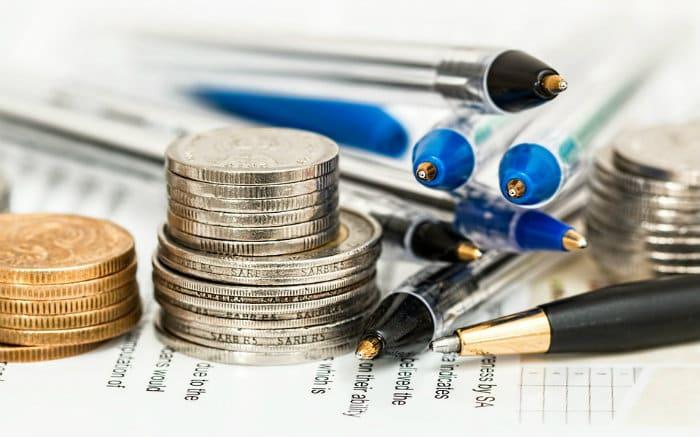 Imagem de moedas e canetas para ilustrar texto sobre consórcio como investimento.
