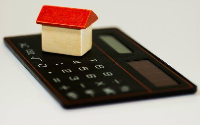 Imagem de calculadora e uma casa em miniatura para ilustrar texto sobre receber carta de crédito em dinheiro