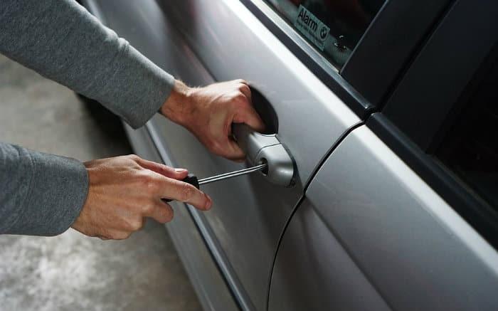 Imagem de pessoa tentando roubar um carro para ilustrar texto sobre seguro somente contra roubo