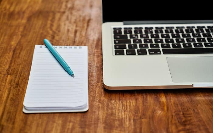 Imagem de um computador, bloco e caneta para ilustrar texto sobre como declarar consórcio no IR.,