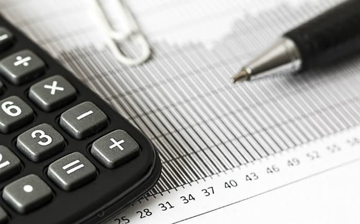 Imagem de calculadora e gráfico para ilustrar texto sobre tipos de seguro garantia.