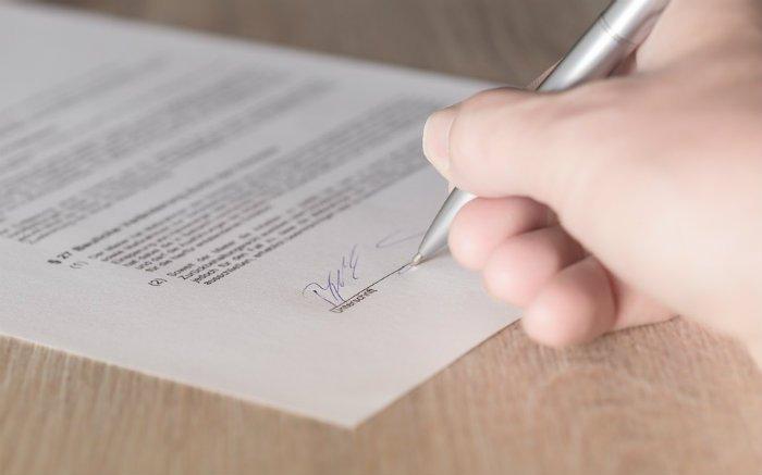 Imagem de pessoa assinando contrato para ilustrar texto sobre comprar carta de crédito contemplada