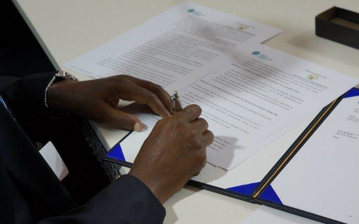 Foto de pessoa assinando um contrato para ilustrar texto sobre sinistro do seguro garantia