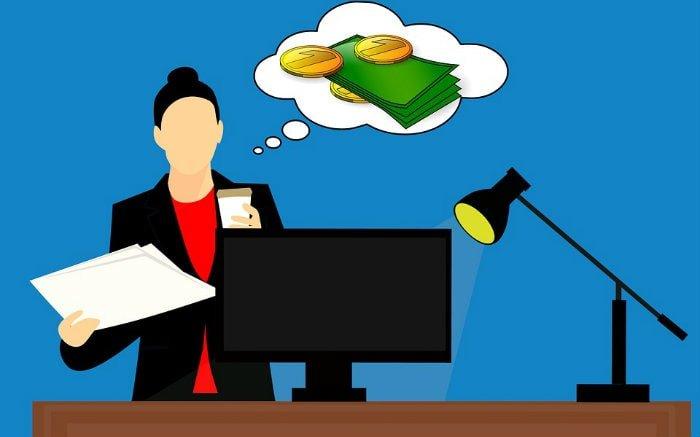 Desenho de pessoa pensando em dinheiro na frente do computador para ilustrar texto sobre consórcio barato.
