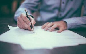 Foto de pessoa lendo um contrato para ilustrar texto sobre contrato de consórcio