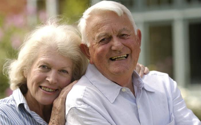 Imagem de casal de idosos sorrindo para ilustrar texto sobre odontogeriatria.