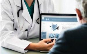 Foto de médico mostrando tela de computador para ilustrar texto sobre como contratar plano de saúde online