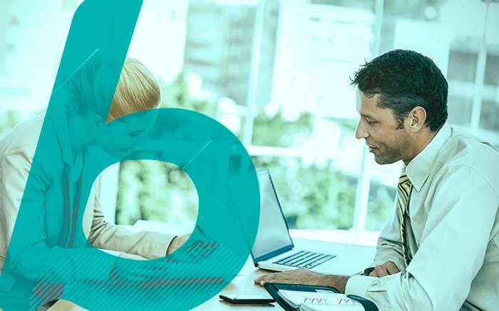 Imagem de pessoas trabalhando no computador e conversando para ilustrar texto sobre sinistro do seguro garantia