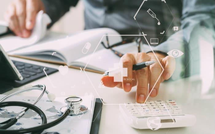 Foto de pessoa fazendo contas e equipamento médico para ilustrar texto que fala se plano com CNPJ é mais barato mesmo.