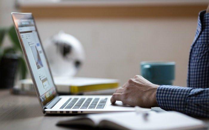 Imagem de pessoa no commputador para ilustrar texto sobre portabilidade de plano de saúde empresarial