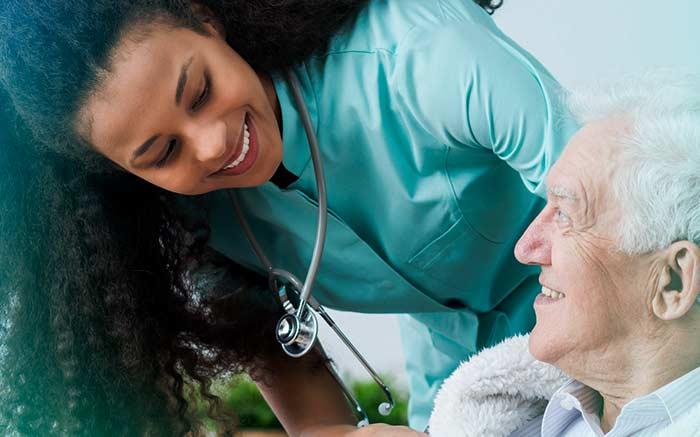 Imagem de cuidadora e pessoa de idade para texto sobre como conseguir home care pelo convênio