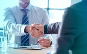 Imagem de pessoas fechando negócio para texto sobre Plano AMIL PME