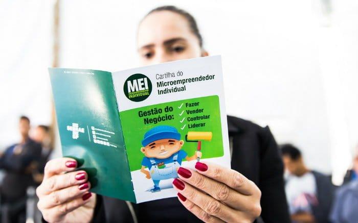 Foto de mulher segurando uma cartilha de MEI para falar sobre as vantagens de ser MEI