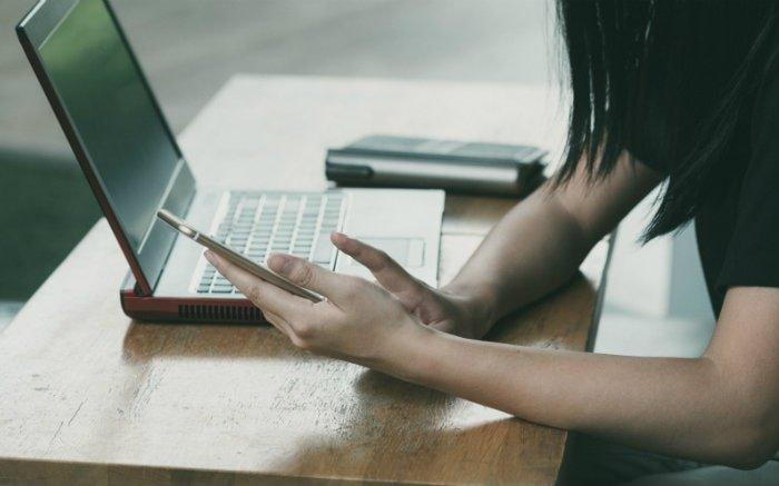 Imagem de pessoa mexendo no computador e celular para ilustrar texto sobre reembolso SulAmérica