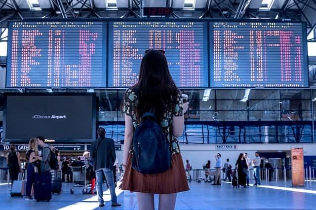 Imagem de uma mulher no aeroporto para ilustrar a postagem de Roupas para viajar de avião.