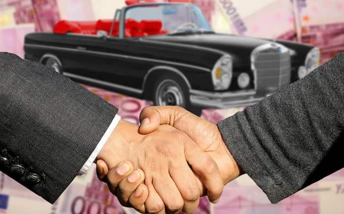 Imagem de pessoas fechando negócio de compra de carro para ilustrar texto sobre carro básico