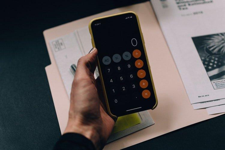 Imagem de uma mão segurando celular aberto na calculadora