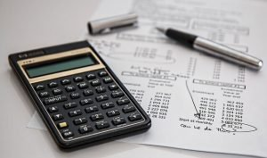 Imagem de mesa com calculadora e papel com contas para ilustrar texto sobre imposto de renda