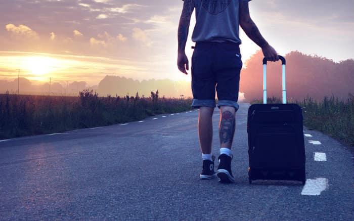 Imagem de homem na estrada com mala para ilustrar texto sobre como cancelar seguro viagem