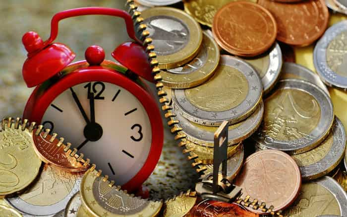 Imagem de relógio e dinheiro para texto sobre a melhor ocasião para o empréstimo empresarial