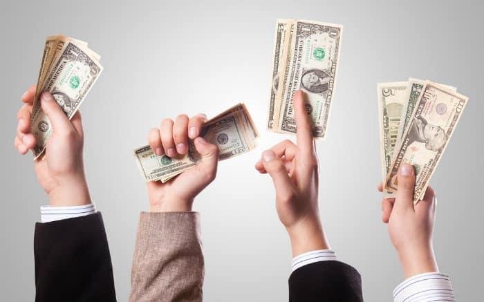 Imagem de mãos com dinheiro para ilustrar texto sobre dicas de empréstimo empresarial